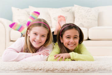 Two girls/friends lying on clean, fresh carpet cleaned with Chem-Dry Green Clean in Bellingham, WA