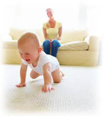 Baby crawling on carpet with lady watching from sofa; Modernistic, Troy