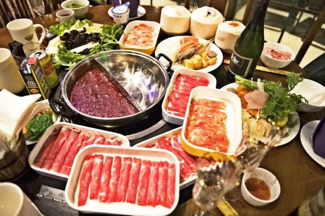 Hot pot table filled with meats, veggies, drinks and 2 kinds of broths