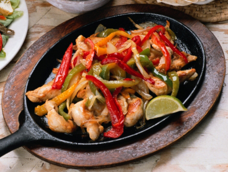 Chicken fajitas dinner with red, green and orange peppers and fancy cut lime.