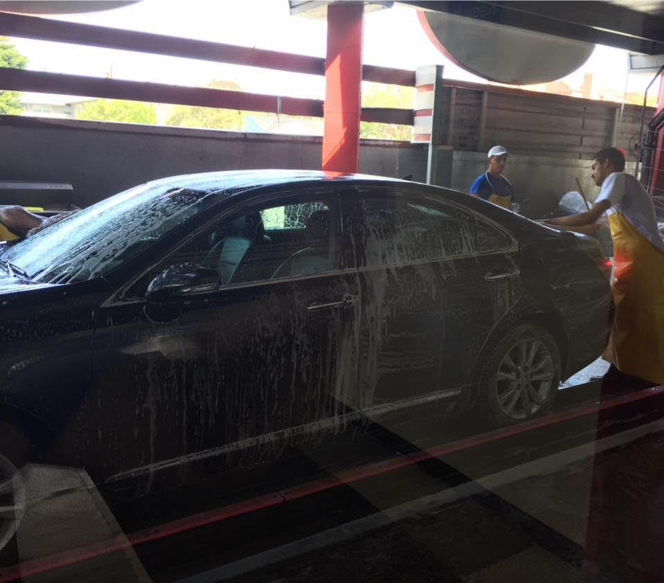black car taking advantage of the full service car wash at circle marina car wash long beach CA