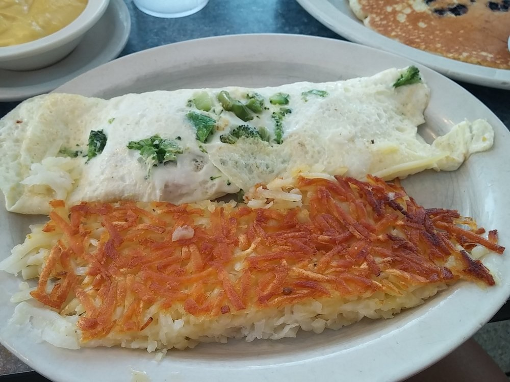 Overstuffed spinach omelet with fried potatoes