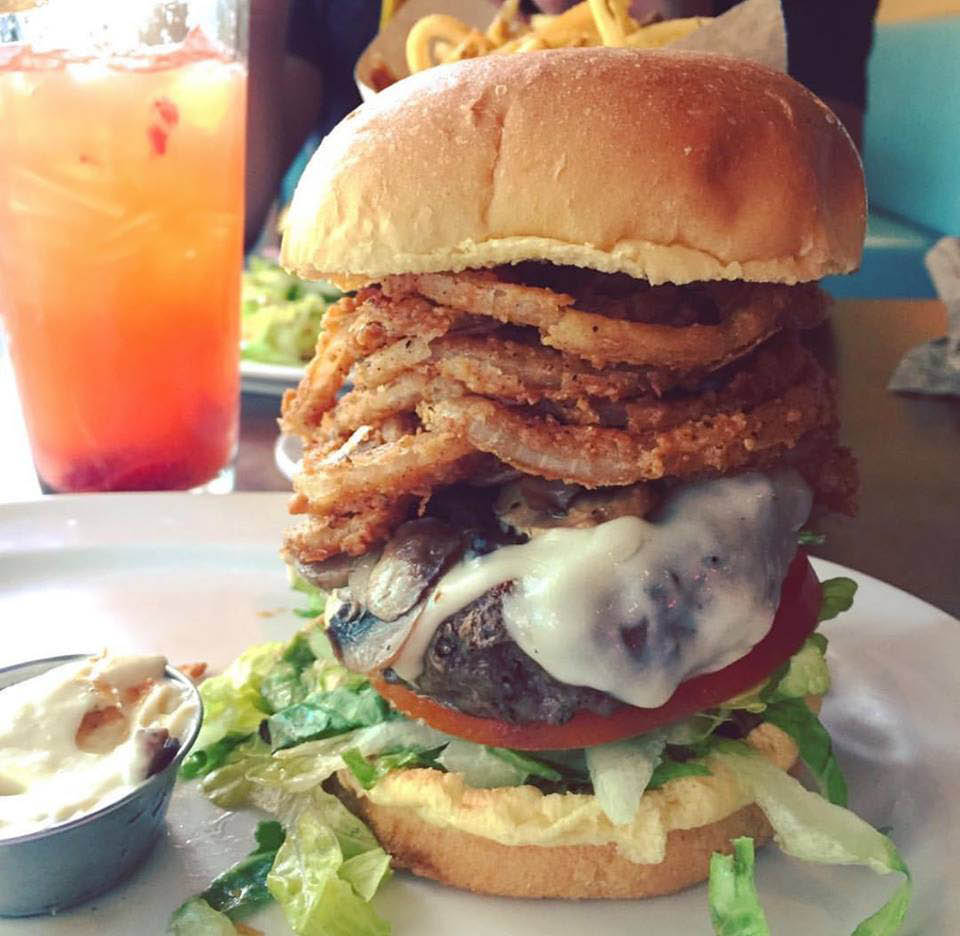 Burger stacked high with onion rights and fried eggs in Houston