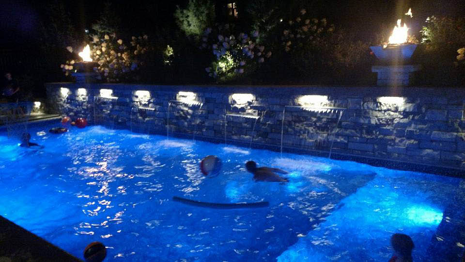 Pool with a stone wall and fire torches with LEDs
