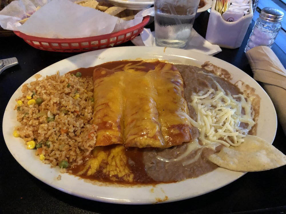 Enchiladas smothered in sauce and cheese with rice