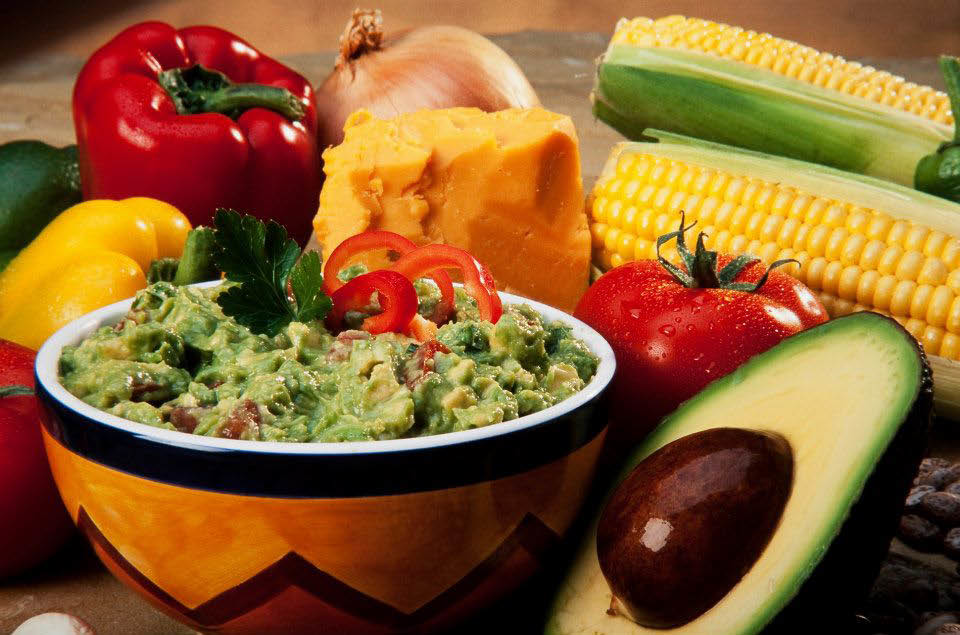 Photo of Guacamole in yellow bowl with red and yellow peppers, corn on the cob and sliced avocado with seed.