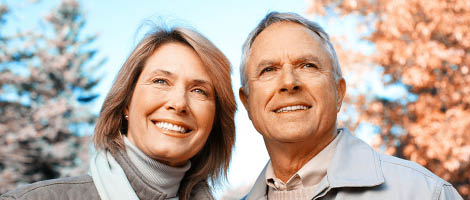 Older couple smiling with dental implants