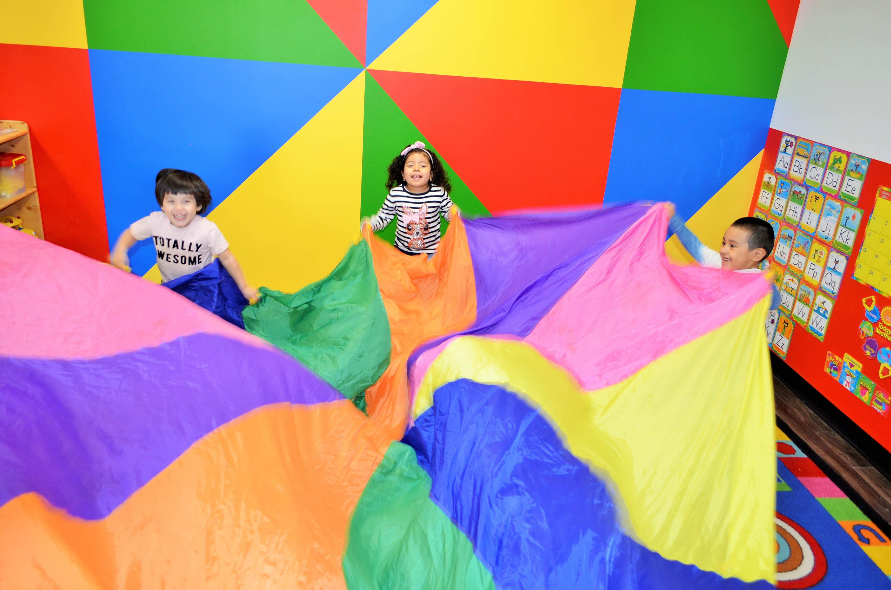 Kids playing on a rainbow parachute.
