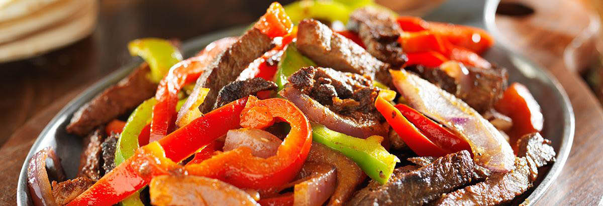 Sizzling steak fajitas with roasted peppers & onions banner