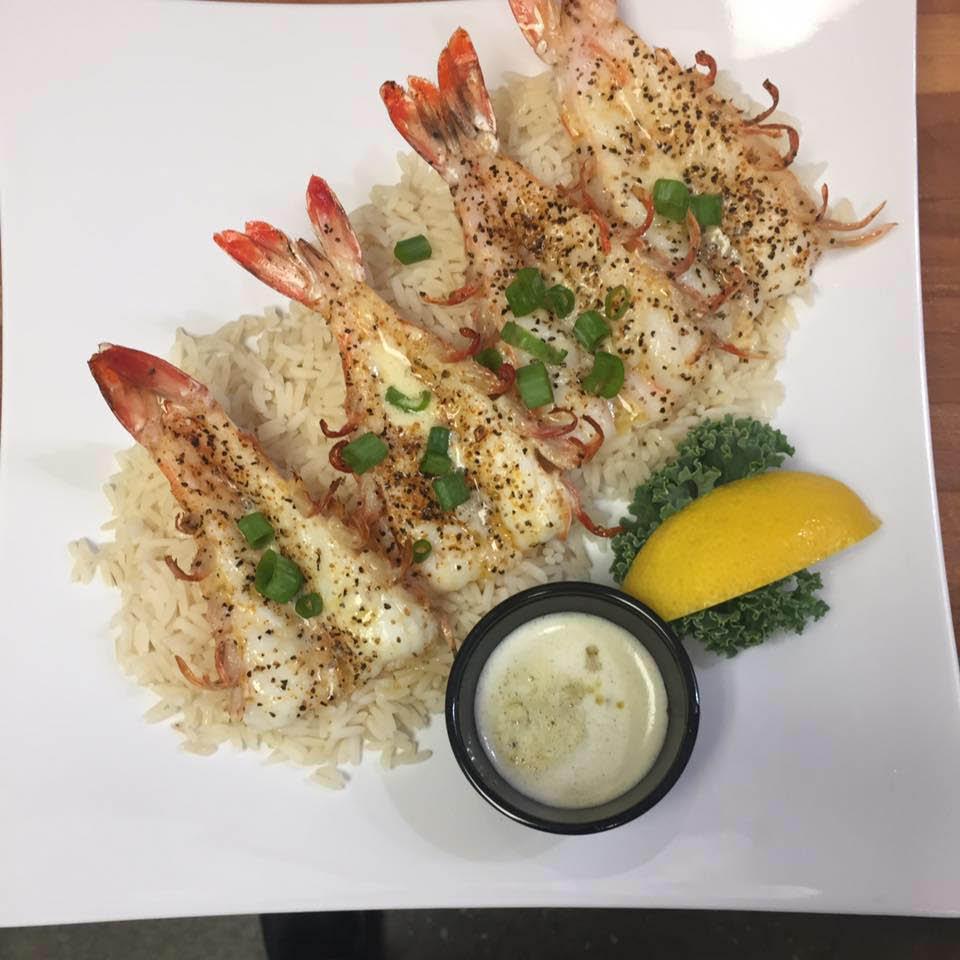 Butterflied pepper shrimp over white rice with homemade white wine cream sauce