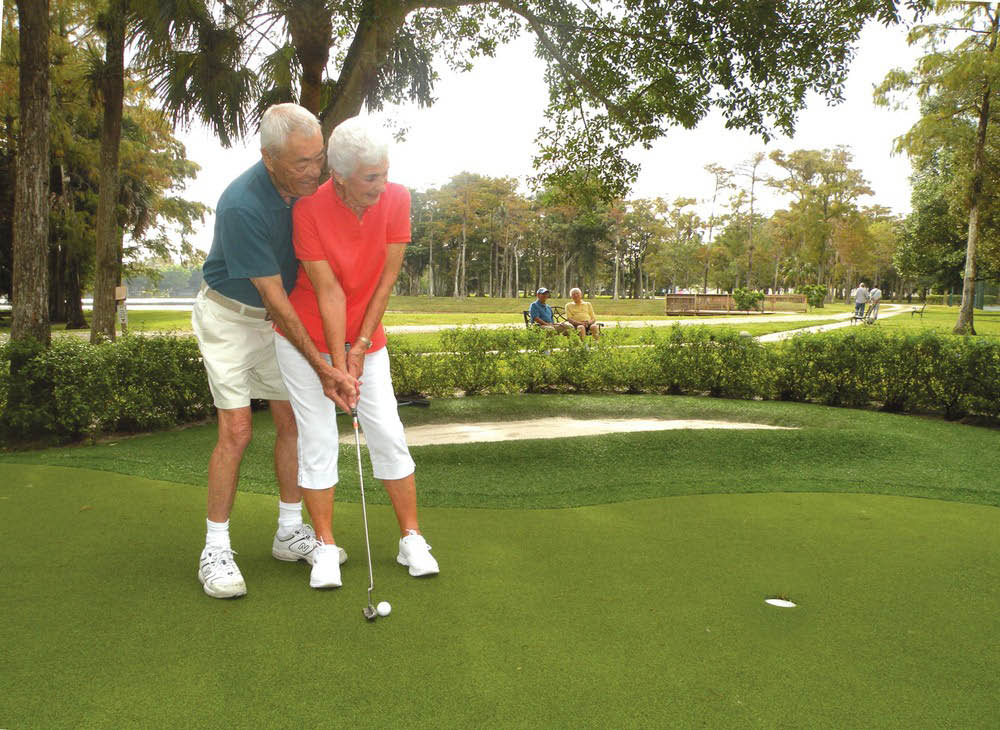 senior couple golfing on putting green at Pacifica Senior Living Forest Trace in Lauderhill