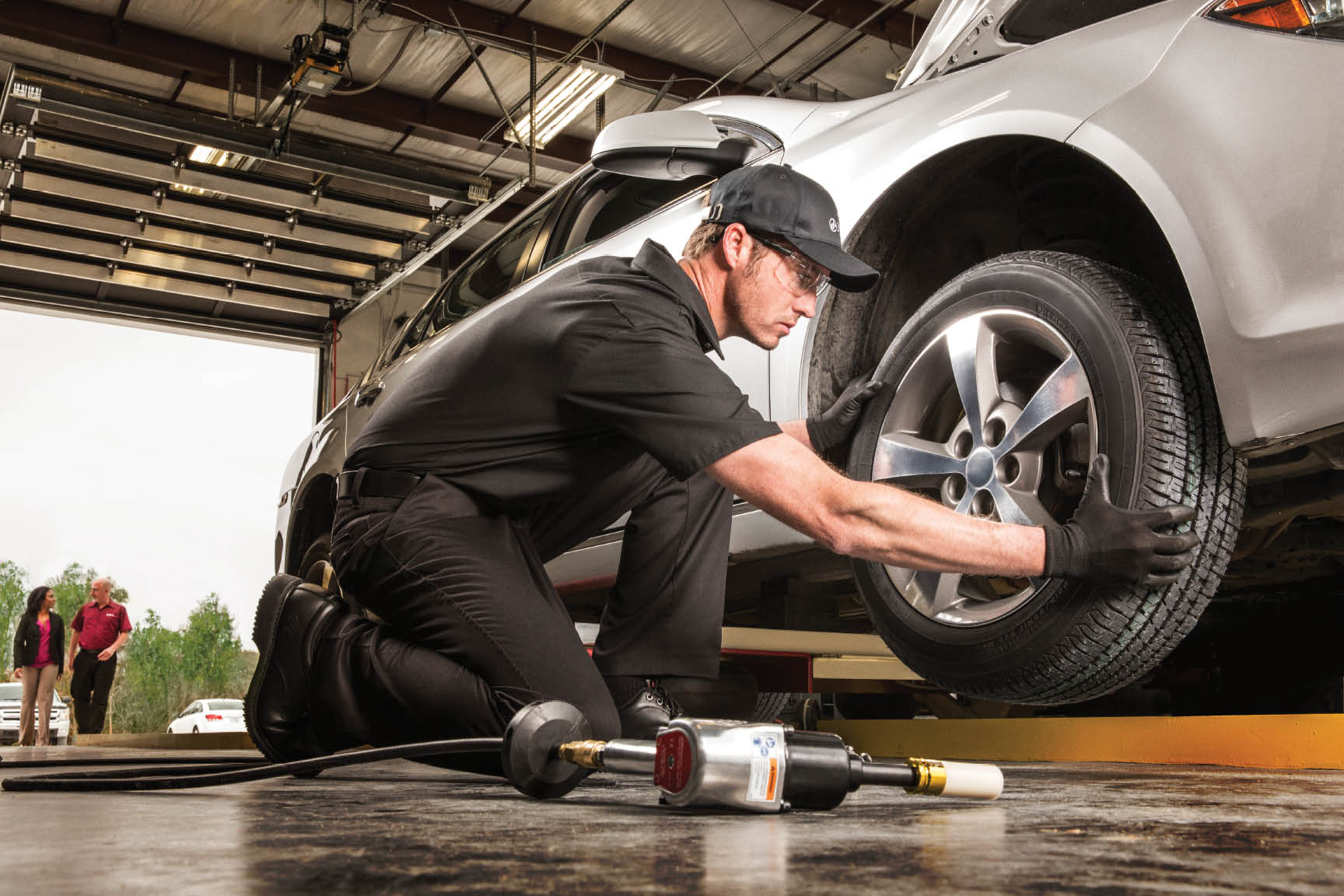 mechanic checking tires; Jiffy Lube offers tire rotation and tire pressure checks