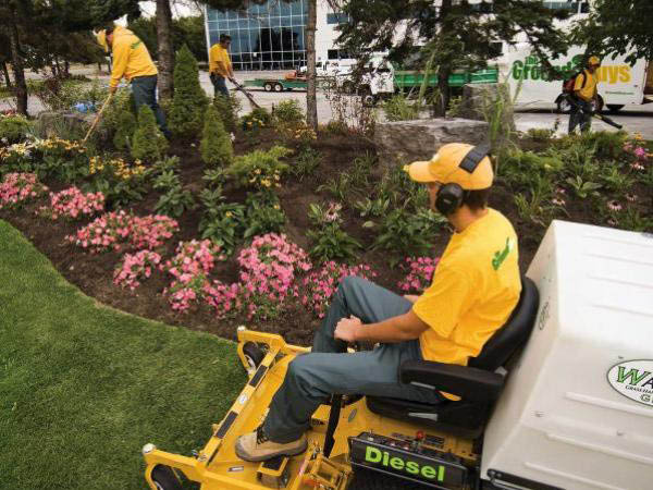 The Grounds Guys Of Overland Park Crew Member Cutting a Customer's Lawn
