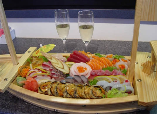 Sushi roll and sashimi platter with accompaniments