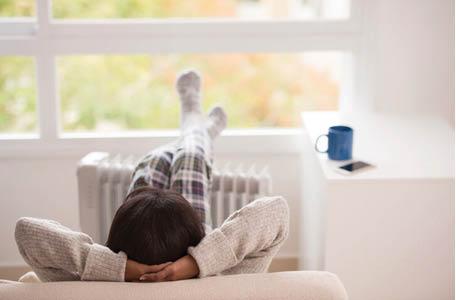 man relaxing at home; heating and cooling companies in Eden, GA; a/c repair in Pembroke, GA