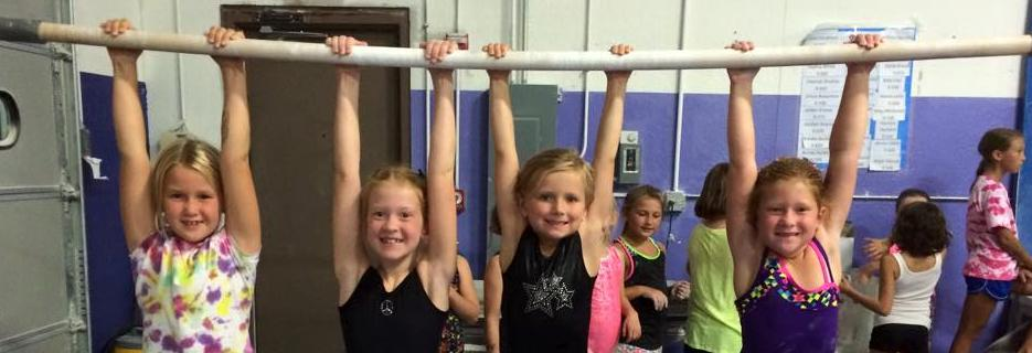 Girls hanging from parallel bar at Gym-Kinetics in Mokena, Il.
