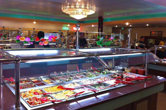 Salad bar with lettuce, veggies, fruit and dressings
