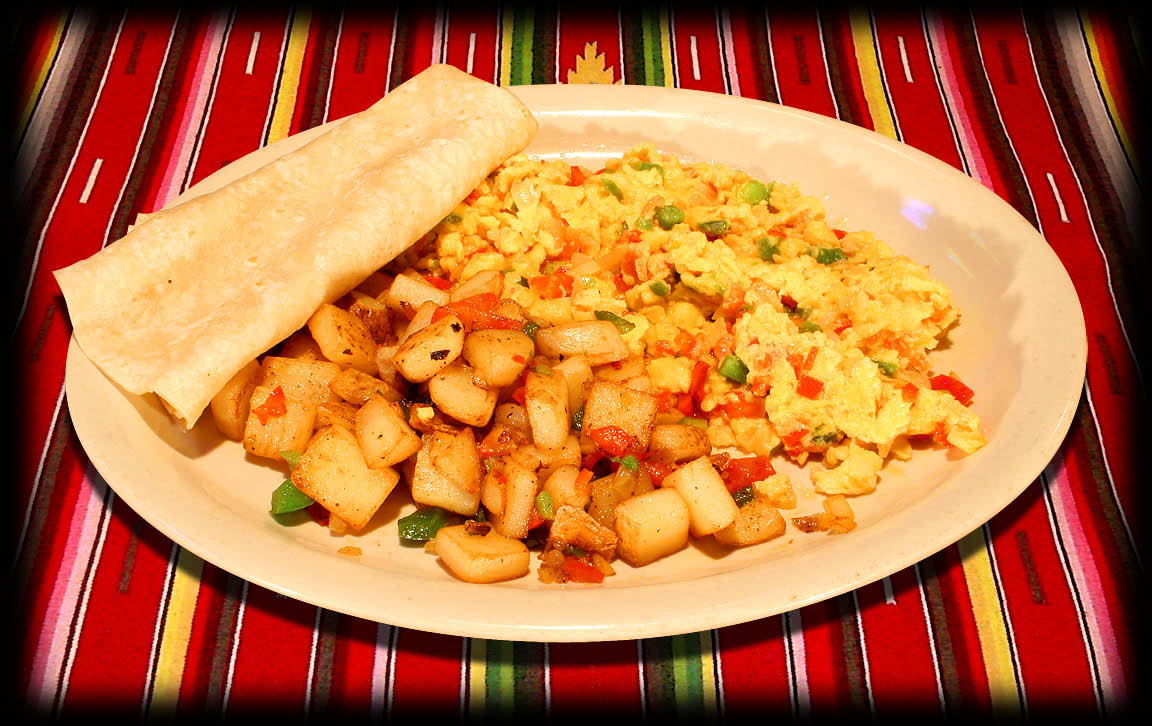 Huevos a la Mexicana  Two scrambled eggs* cooked with diced tomatoes, red & green peppers and onions, served with your choice of ham, bacon or chorizo and with your choice of Mexican potatoes or beans and rice with a warm flour tortilla.