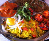 full plate of Indian food, including yellow rice, tomatoes, curry
