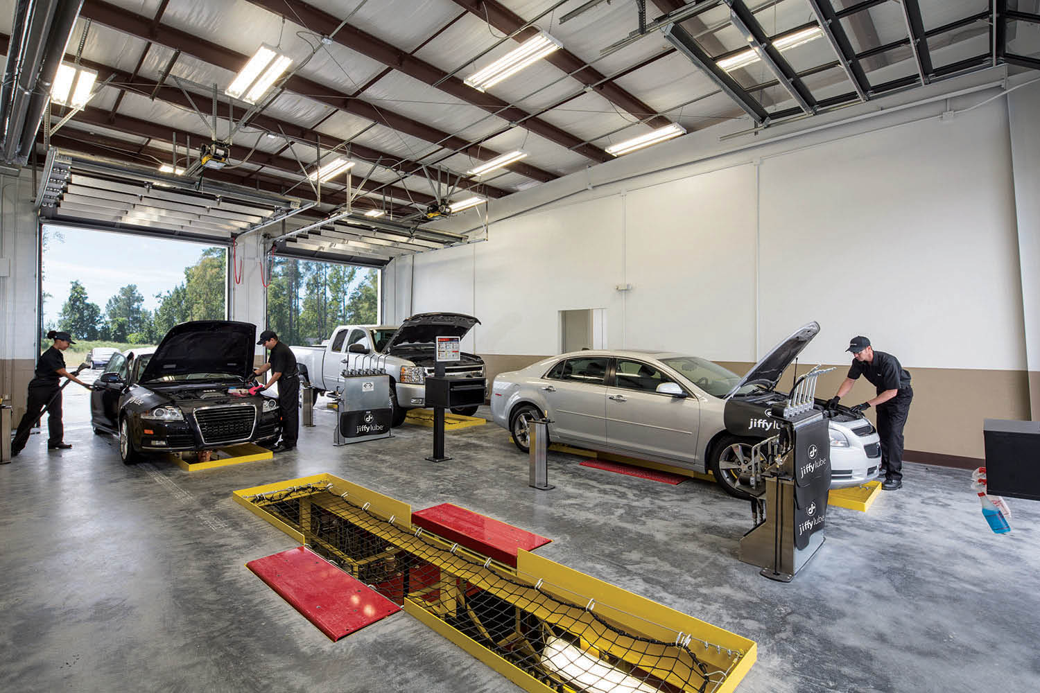 Jiffy Lube auto technicians working on cars in the garage