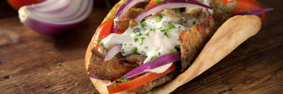 Kronos Gyros with onion, tomato and tzatziki sauce.