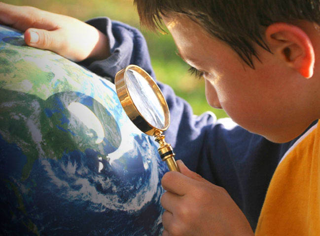 Young boy in a orange and blue shirt using a magnifying glass to inspect a world globe.