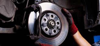 hand of an auto repair technician at Los Amigos Tire Services adjusting a brake cylinder on a car