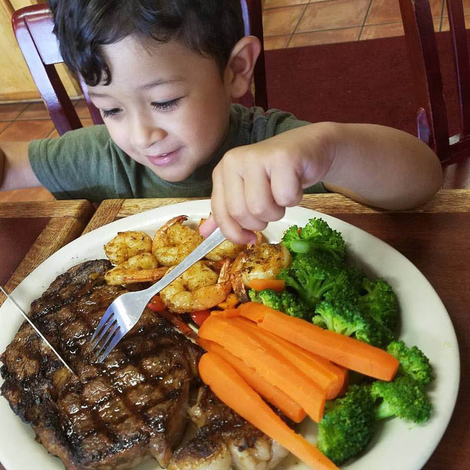 Happy customer eating their first steak in Houston