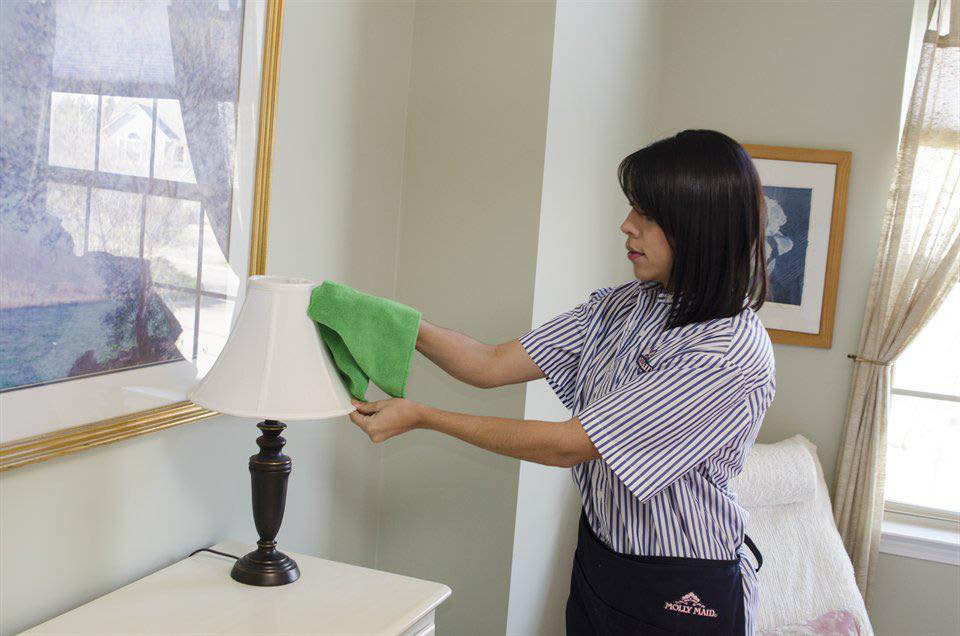 Maid dusting off green lamp shade