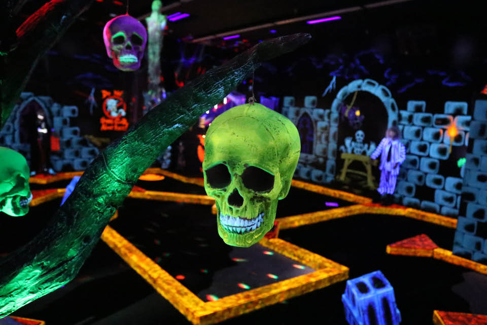 Neon skull hanging from a tree at Monster Mini Golf