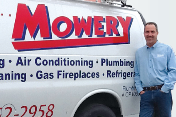 Mowery service truck with owner leaning against the back