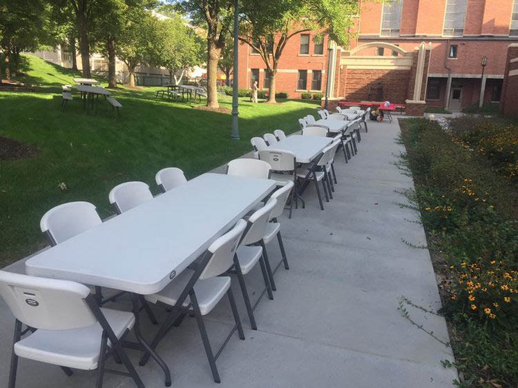long line of long tables with chairs for outdoor event; Mr. Picnic in Nebraska