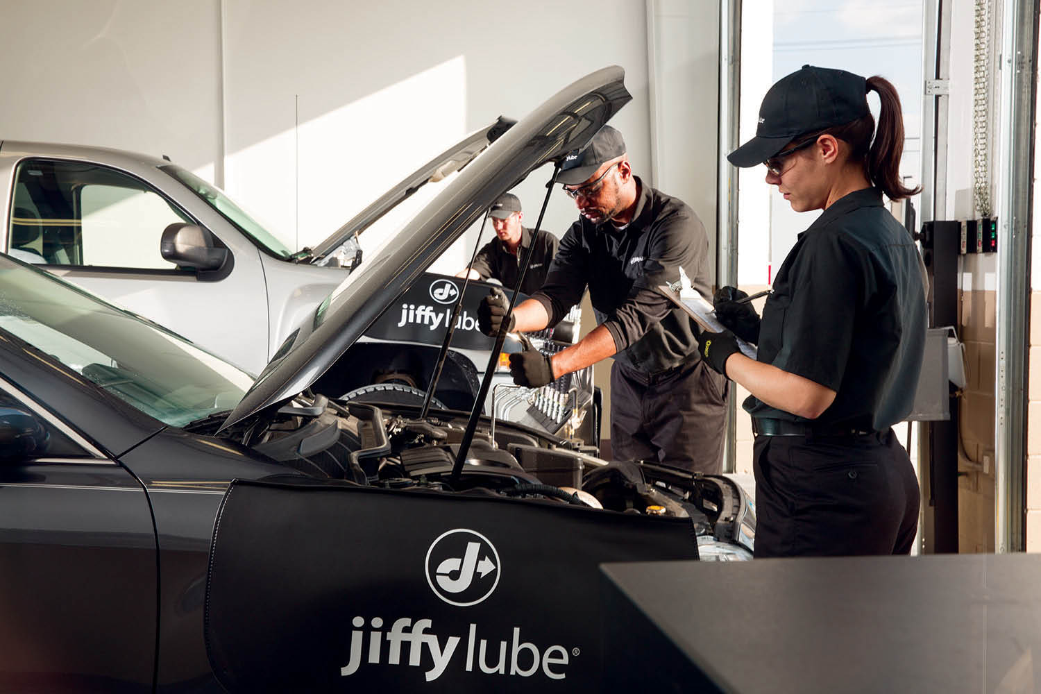 female auto mechanic at Jiffy Lube performing routine auto maintenance