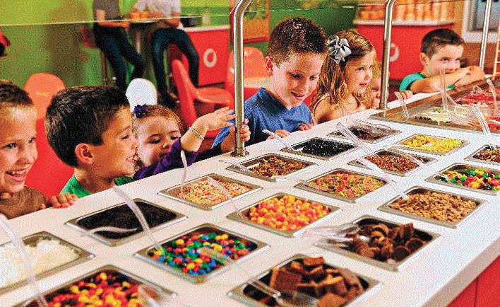 Kids looking at all the toppings at Orange Leaf in Macomb, MI