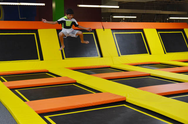 Child jumping in trampoline park.