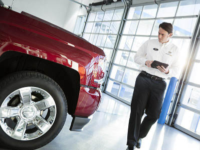 Outten salesperson examining car on the showroom floor.