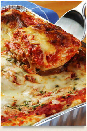 Tray of Lasagna with slice being served.