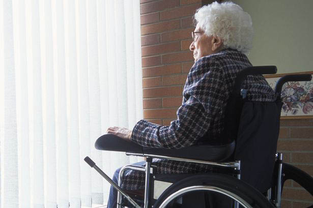 patient sitting in a wheel chair by a window