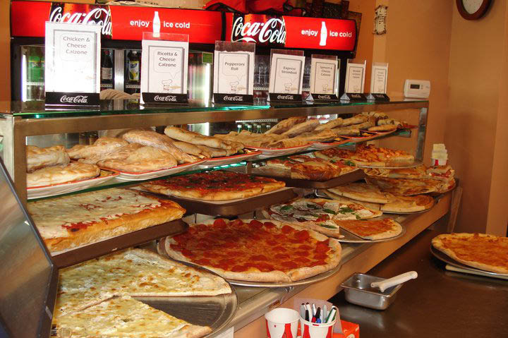 Display of specialty pizzas, hand-tossed and Sicilian pies