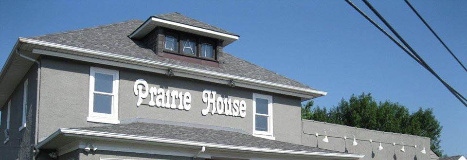 The Prairie House exterior photo of large gray house restaurant banner