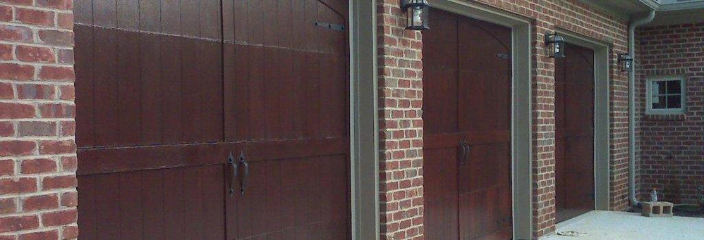 Brick home with dark wood triple garage doors banner
