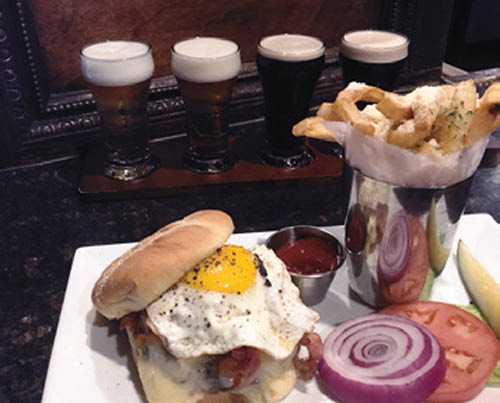 Fried egg burger with parmesan fries and a row of craft beers.