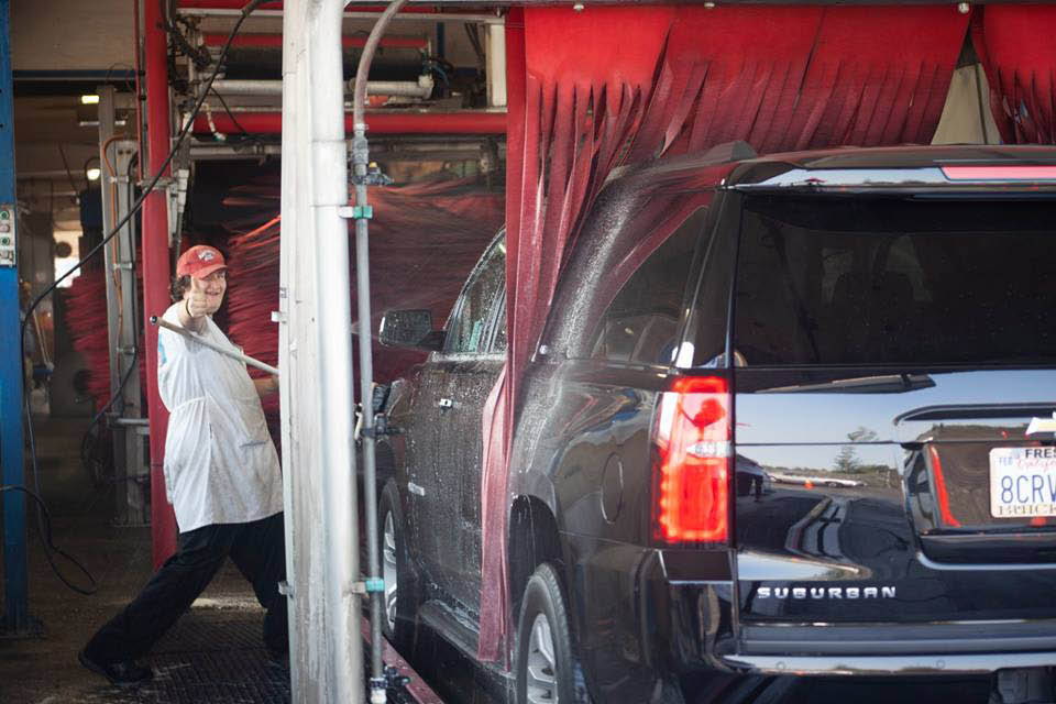 red carpet car wash attendant guides you through state-of-the-art auto washing station