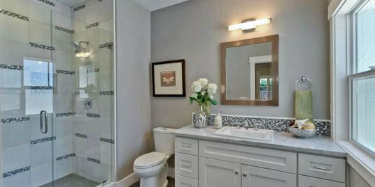 remodeled bathroom in cream and white with light over the vanity mirror.