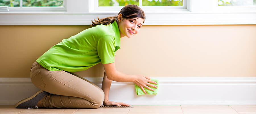 maid cleaning baseboards