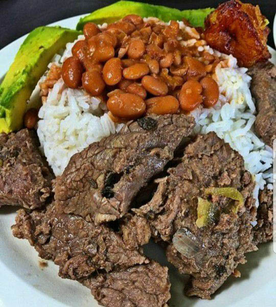 Rice and beans plus tender seasoned meats at Rincon Dominicano by Luisito