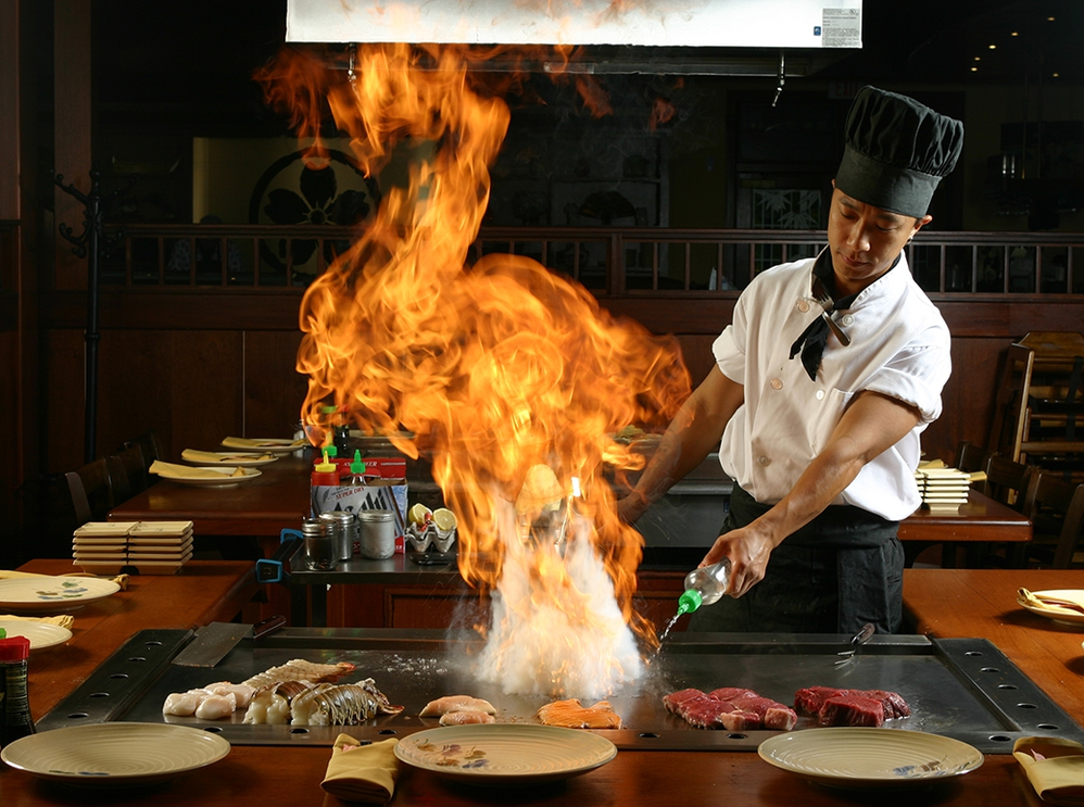 Expert chef cooks with flame tableside on hibachi grill at Sakura