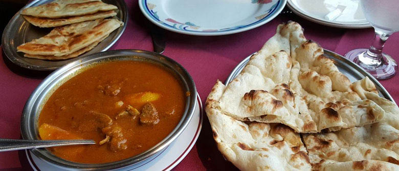 Indian food with platters of Naan Bread