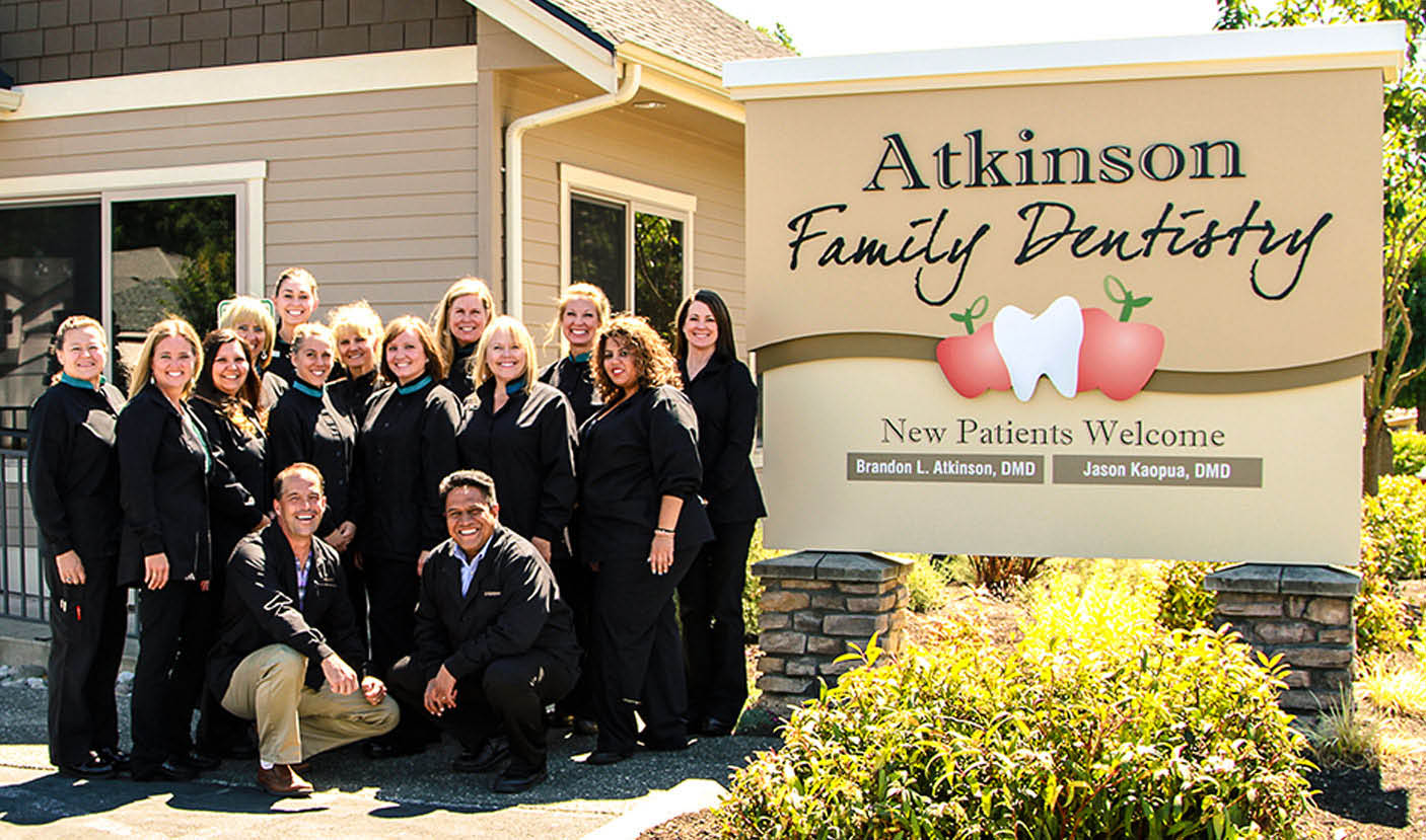 Atkinson Family Dentistry team photo in front of their new building sign