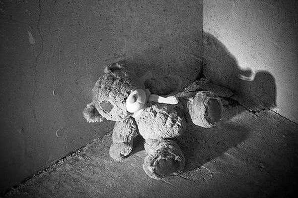 Photo of an old bear stuffed animal sitting in the corner in Kenosha, WI